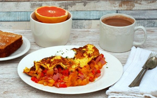 Farmers Omelette wraps diced sweet red peppers, sweet onion, hash browns, Canadian bacon, and cheese in fluffy eggs for a hearty breakfast with serious staying power to keep you going all morning long.